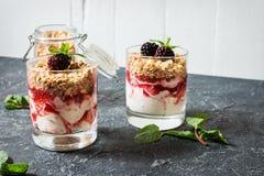 Zdrowy płatowaty deser z jogurtem, granola, dżem, czernica w szkle na kamiennym tle fotografia stock