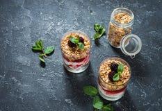 Zdrowy płatowaty deser z jogurtem, granola, dżem, czernica w szkle na kamiennym tle zdjęcia royalty free