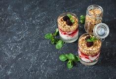 Zdrowy płatowaty deser z jogurtem, granola, dżem, czernica w szkle na kamiennym tle zdjęcia stock