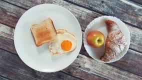 Zdrowy smakowity śniadanie: smażący jajko, grzanka, jabłko i croissant, zdjęcie wideo