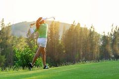 zdrowy sport Azjatycki Sporty kobieta golfisty gracz robi golfa hu?tawkowemu tr?jnikowi daleko na zielonym wiecz?r czasie, przypu obrazy royalty free