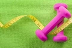 Zdrowy styl życia, sprawności fizycznej i ciężaru kontrolny pojęcie z zbliżenie menchią na pary dumbbells z pomiarową taśmą zawij zdjęcie stock