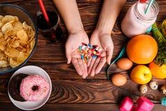 Zdrowy styl życia, fast food lub leki Pastylki w rękach, pączku i świeżej owoc, Fotografia Stock