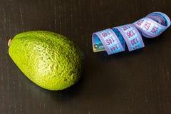 Zdrowy styl życia pojęcie, avocado i pomiarowa taśma na czarnym tle, zdjęcia stock