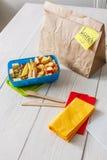 Zdrowy szkolny lunch w pudełku na białym drewno stołu tle Zdjęcia Stock