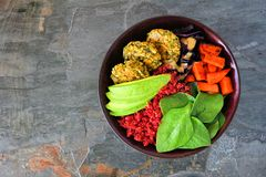 Zdrowy weganinu Buddha puchar z falafels, ćwikłowym quinoa, avocado i warzywami, odgórny widok na zmroku kamienia tle obraz royalty free