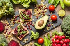 Zdrowy weganinu jedzenie Kanapki i świezi warzywa na drewnianym tle obrazy stock