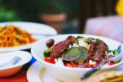 Zdrowy weganinu jedzenie - zbliżenie sałatka z sundried pomidorami, bryka liście Fotografia Stock
