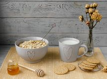 Zdrowy wholegrain śniadanie: oatmeal, mleko, ciastka, miód i waza z różami, Fotografia Royalty Free