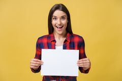 Zdumienie lub zdziwiona kobieta z pustym białym panelem, odosobnionym na żółtym tle zdjęcie stock