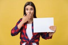 Zdumienie lub zdziwiona kobieta z pustym białym panelem, odosobnionym na żółtym tle obraz stock