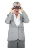 Zdumiewający bizneswoman patrzeje coś przez lornetek Fotografia Stock