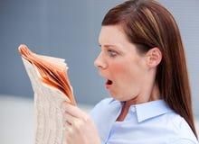 zdumiewający bizneswomanu gazety czytanie Fotografia Stock