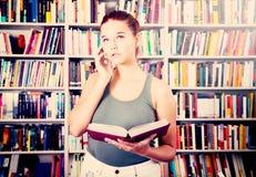 Zdumiona dziewczyna wybiera książkę w bibliotece Fotografia Royalty Free