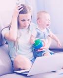 Zdumiona matka ma zagadnienie z pracą podczas gdy dzieciaka płacz Obrazy Royalty Free
