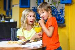 Zdziweni dziewczyn spojrzenia przy chłopiec pije sok Zdjęcie Stock