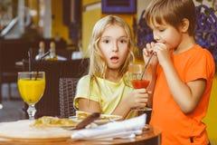 Zdziweni dziewczyn spojrzenia przy chłopiec pije sok Zdjęcia Royalty Free