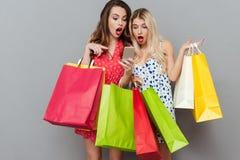 Zdziweni młoda dama przyjaciele z torba na zakupy używać telefon komórkowego Fotografia Stock