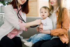Zdziwiona śliczna dziewczynka sprawdza żeńską lekarką używa stetoskop w klinice fotografia stock