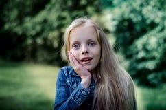 Zdziwiona śliczna mała blond dziewczyna przy lata polem Obrazy Stock