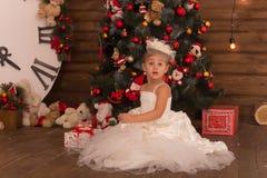 Zdziwiona śliczna mała dziewczynka w białej ładnej sukni z teraźniejszością zdjęcie stock