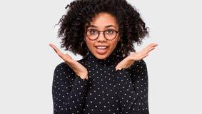 Zdziwiona Afro młoda kobieta zadziwiał wyrażenie Piękna kobieta słucha coś zadziwiać, utrzymania ręki otwierają szerokiego emocje fotografia stock