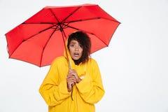 Zdziwiona afrykańska kobieta w deszczowu pozuje z parasolem Obraz Stock