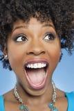 Zdziwiona amerykanin afrykańskiego pochodzenia kobieta patrzeje daleko od z usta otwartym Obraz Royalty Free