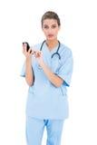 Zdziwiona brown z włosami pielęgniarka w błękicie szoruje używać telefon komórkowego zdjęcia stock