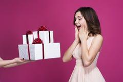 Zdziwiona brunetka w różowej sukni bierze mnóstwo prezenty zdjęcia stock