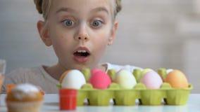 Zdziwiona dziewczyna pojawiać się spod stołowych i patrzeją kolorowych Wielkanocnych jajek zbiory wideo