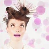 Zdziwiona dziewczyna z galanteryjną fryzurą przy białym zamazanym tłem fotografia stock