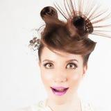 Zdziwiona dziewczyna z galanteryjną fryzurą przy białym zamazanym tłem zdjęcie stock