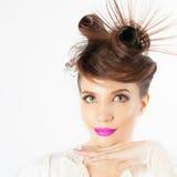 Zdziwiona dziewczyna z galanteryjną fryzurą przy białym zamazanym tłem obraz royalty free