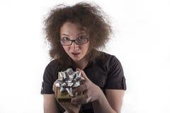 Zdziwiona Frizzy Z włosami dziewczyna Trzyma prezent Zdjęcia Stock