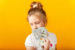 Zdziwiona i radosna dziewczyna trzyma dolary w ich rękach i zakrywa ich twarz zdjęcia stock