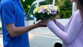 Zdziwiona kobieta bierze bukiet od kurier ręk, kwiatu sklepu dostawa obraz stock