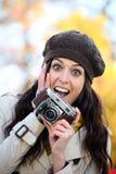Zdziwiona kobieta bierze fotografie w jesieni zdjęcia royalty free
