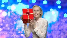 Zdziwiona kobieta egzamininuje prezenta pudełko zbiory wideo