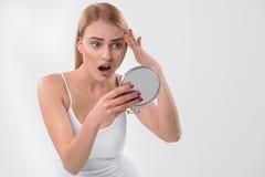 Zdziwiona kobieta obserwuje jej twarzową skórę Zdjęcie Royalty Free