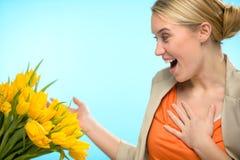 Zdziwiona kobieta otrzymywa bukiet żółci tulipany zdjęcia royalty free
