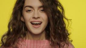Zdziwiona kobieta patrzeje in camera na kolorze żółtym Portret szokująca kobieta w studiu zdjęcie wideo