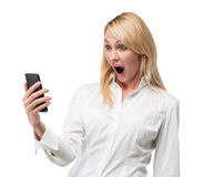 Zdziwiona kobieta patrzeje telefon komórkowego obrazy royalty free