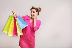 Zdziwiona kobieta pozuje z torbami na zakupy i patrzeje kamerę zdjęcia stock