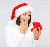 Zdziwiona kobieta w Santa pomagiera kapeluszu z prezenta pudełkiem Fotografia Royalty Free