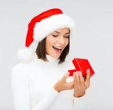 Zdziwiona kobieta w Santa pomagiera kapeluszu z prezenta pudełkiem Obrazy Stock