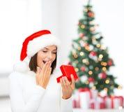 Zdziwiona kobieta w Santa pomagiera kapeluszu z prezenta pudełkiem Obraz Royalty Free