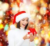 Zdziwiona kobieta w Santa pomagiera kapeluszu z prezenta pudełkiem Zdjęcia Stock