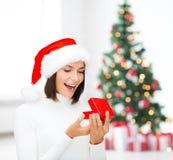 Zdziwiona kobieta w Santa pomagiera kapeluszu z prezenta pudełkiem Obraz Stock