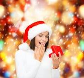 Zdziwiona kobieta w Santa pomagiera kapeluszu z prezenta pudełkiem Zdjęcia Royalty Free